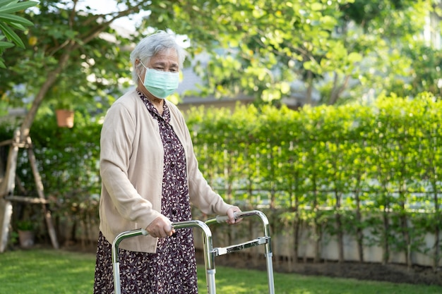 Asian senior or elderly old lady woman walk with walker and wearing a face mask for protect safety infection covid-19 coronavirus.