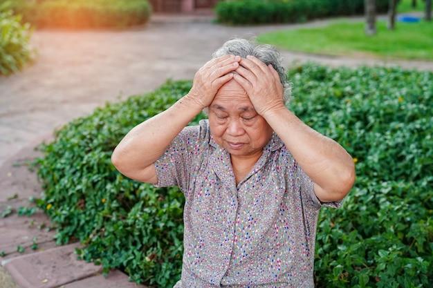 Asian senior or elderly old lady woman with headache