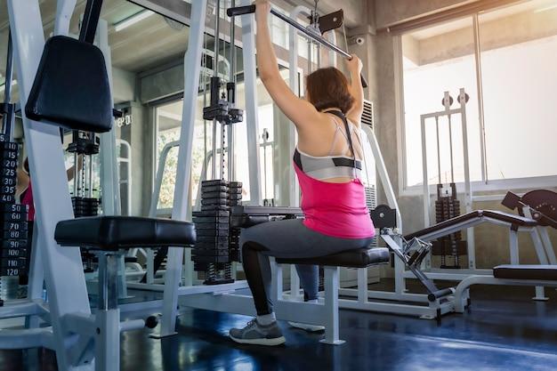 スポーツウエアトレーニングジムでマシンに戻ってでアジアのシニア脂肪女性。