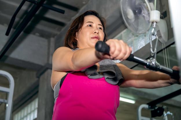 Asian senior fat woman in sportswear training arm with machine at gym.