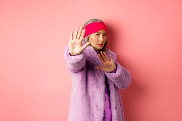 Азиатская старшая женская модель в стильном фиолетовом зимнем пальто стоит в позе жертвы, протягивает руку в жесте остановки и умоляет о пощаде