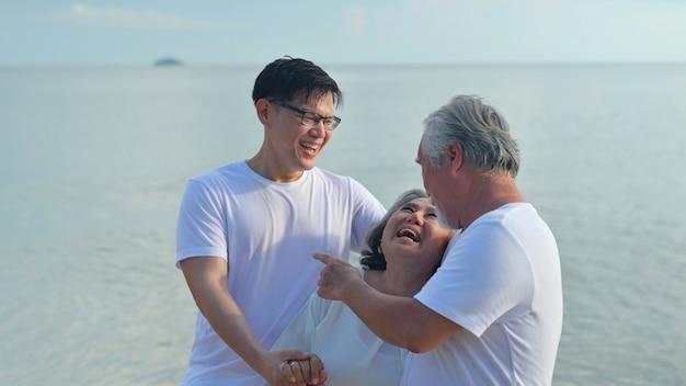 息子と一緒にアジアのシニア愛のカップルがビーチを旅します。夏休みの定年家族のリラックスとレクリエーション。
