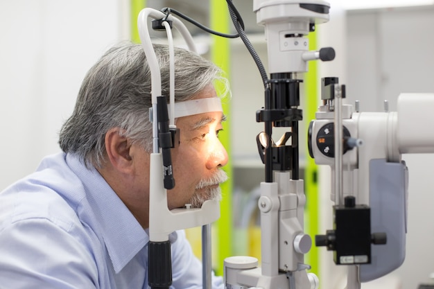 Asian senior male patient having him eyes examined by laser machine