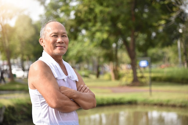 Asian senior male posing with arms crossed.