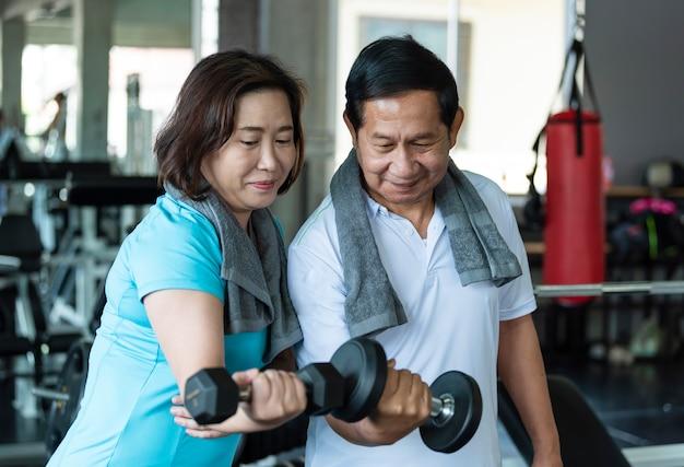 아시아 노인 남성과 여성은 피트니스 체육관에서 아령을 드는 운동을 합니다. 노인의 건강한 생활 방식.