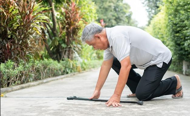 重症筋無力症のために裏庭で家に倒れるアジアの年配の男性