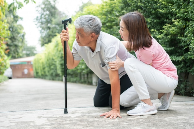 Asian senior man falling down at home in the backyard and the nurse came to help support.