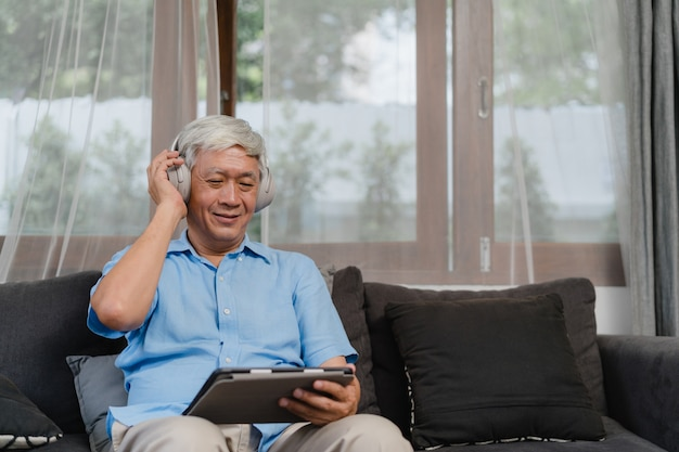 Asian senior man relax at home. asian older male happy wear headphone using tablet listening podcast while lying on sofa in living room at home concept.