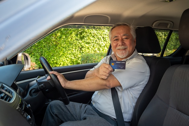 Asian senior man sitting in car and holding credit card.