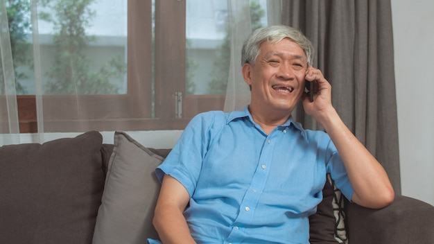Asian senior man talk on phone at home. asian senior older chinese male using mobile phone talking with family grandchild kids while lying on sofa in living room at home concept.