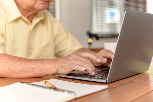 Asian senior man using laptop and looking for insurance after retirement. grandfather stay alone at home.