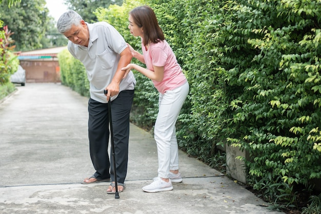 Asian senior man walking in the backyard and the daughter came to help support