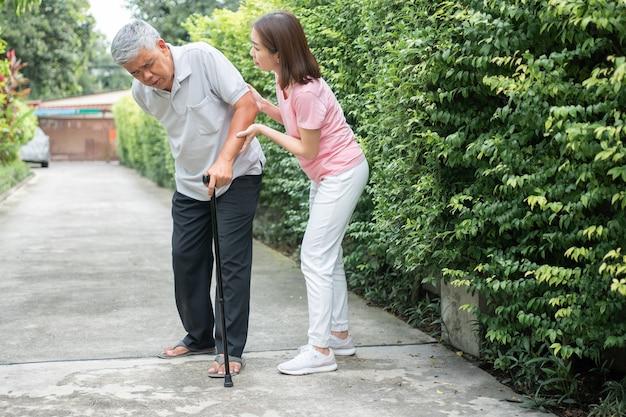 Азиатский пожилой мужчина гуляет на заднем дворе, и дочь пришли поддержать