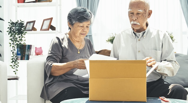 Asian senior man and woman open box with smile face.