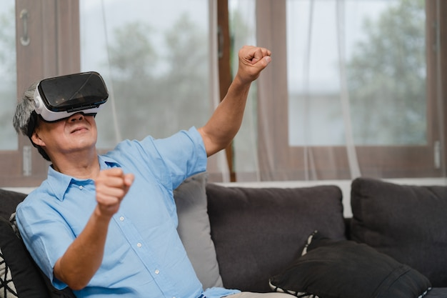 Asian senior men play games at home. asian senior older chinese male happy fun and virtual reality, vr playing games while lying sofa in living room at home concept.