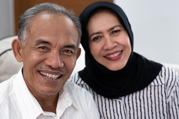 カメラを見てアジアシニアイスラム教徒のカップル