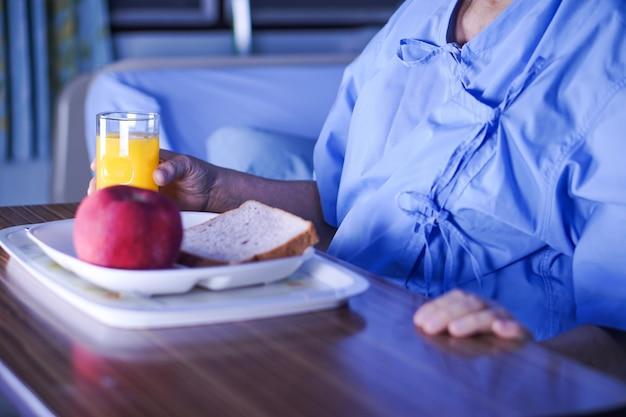 アジアの高齢者女性の女性患者病院で朝食健康的な食べ物を食べる。