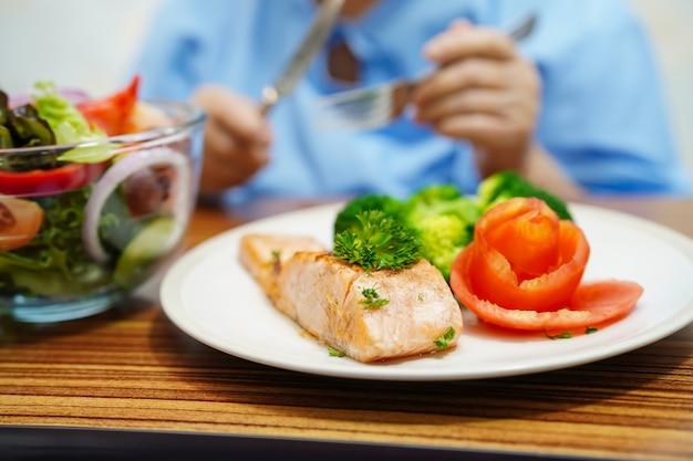 アジアのシニア老婦人女性患者が病院で朝食健康食品を食べる。