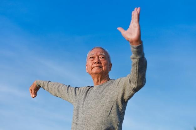 Азиатский старший старик практикует тайцзицюань китайское кунг-фу на пляже