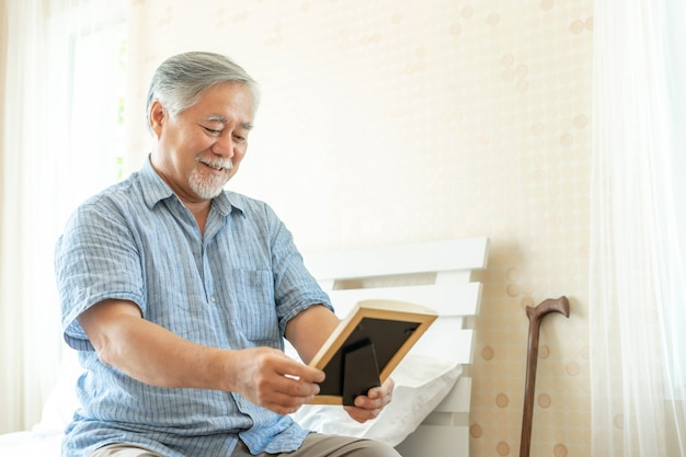 Asian senior old man sat on the bed , he was holding a photograph of his lover in his hand , he looked at it and smiled happily - lifestyle senior elderly people concept