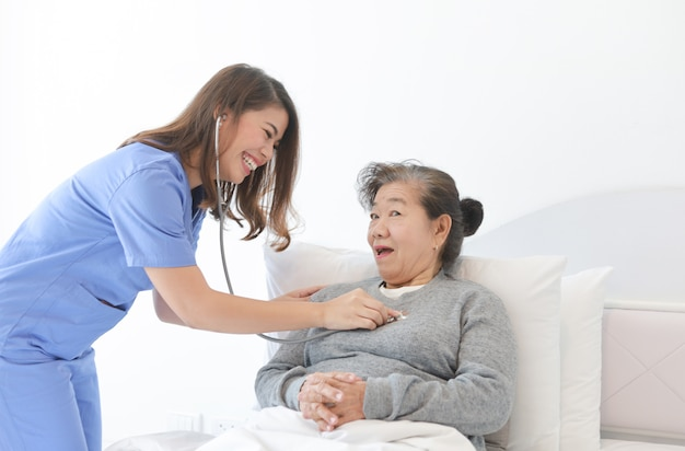 Asian senior old woman on the bed with doctor and her son in hospital