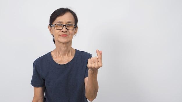 Asian senior or older woman doing miniheart hand sign on white background.