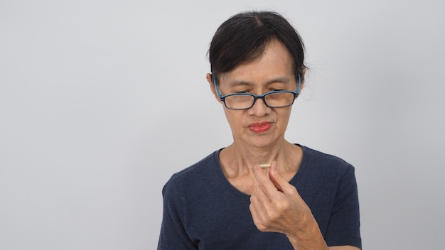 Asian senior or older woman had a back pain posture on white background.