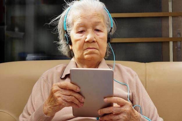 アジアのシニアまたは高齢の老婦人女性は、タブレットから音楽を(使用または再生して)聞くことを楽しんでいます。ヘルスケア、医療、技術の概念。