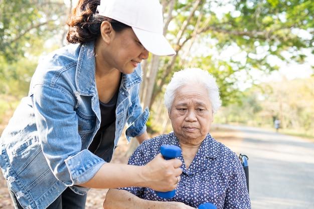 アジアのシニアまたは高齢の老婦人女性が公園でダンベルを使って運動します。