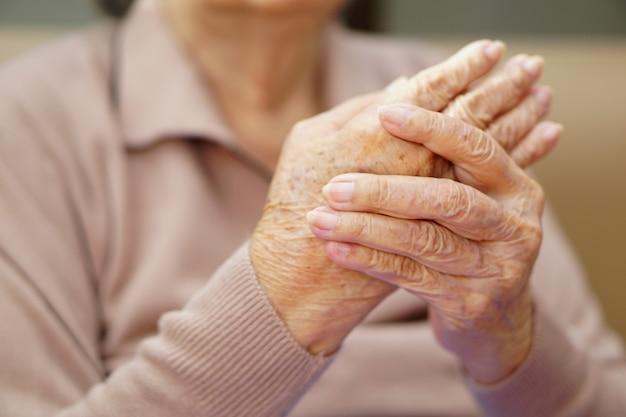 アジアのシニアまたは高齢の老婦人女性が自宅で痛みから手をこねています。ヘルスケア、愛、ケア、励まし、共感。