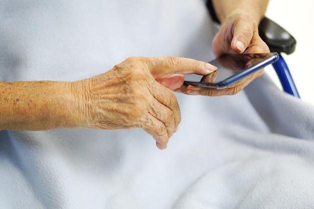アジアの高齢者または高齢の老婦人女性は、車椅子に座って携帯電話を使用または遊んでいます。ヘルスケア、医療、技術の概念。