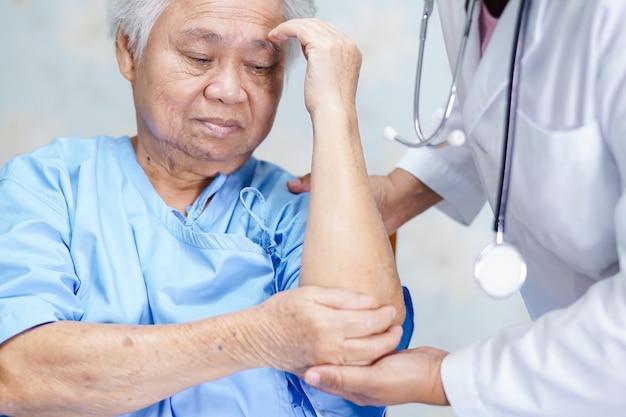 Азиатский старший или пожилой пациент пожилой женщины чувствует боль в локте на кровати в палате больницы, здоровая сильная медицинская концепция.