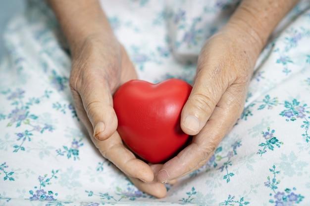 看護病棟のベッドで赤いハートを手に持つアジアの高齢者または高齢の老婦人女性患者、健康的な強力な医療コンセプト