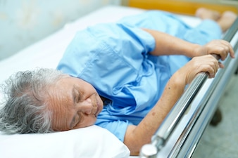 Asian senior or elderly old lady woman patient lying on bed in nursing hospital.