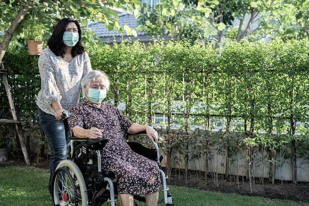 Азиатский старший или пожилой пациент пожилой женщины на инвалидной коляске в парке, здоровая сильная медицинская концепция. здоровая сильная медицинская концепция