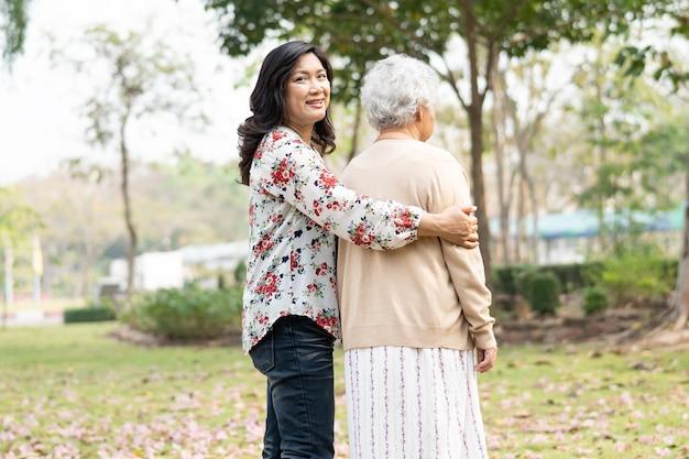 Азиатский старший или пожилой пациент пожилой женщины на инвалидной коляске в парке, здоровая сильная медицинская концепция.