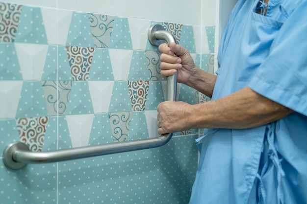 アジアのシニアまたは高齢の老婦人女性患者は、看護病棟のトイレバスルームハンドルセキュリティ、健康的な強力な医療コンセプトを使用しています。
