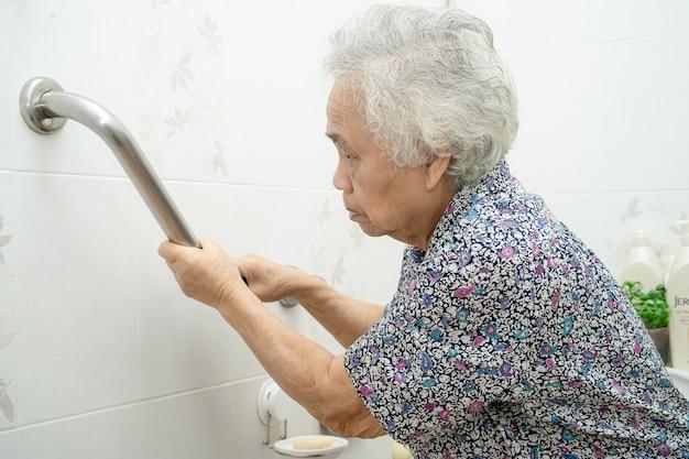 アジアの高齢者または高齢の老婦人女性患者が看護病棟のトイレバスルームハンドルセキュリティを使用