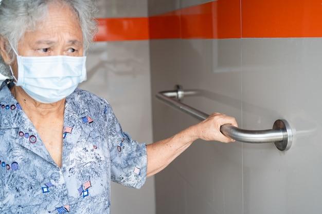 アジアのシニアまたは高齢の老婦人女性患者はトイレのバスルームハンドルのセキュリティを使用します