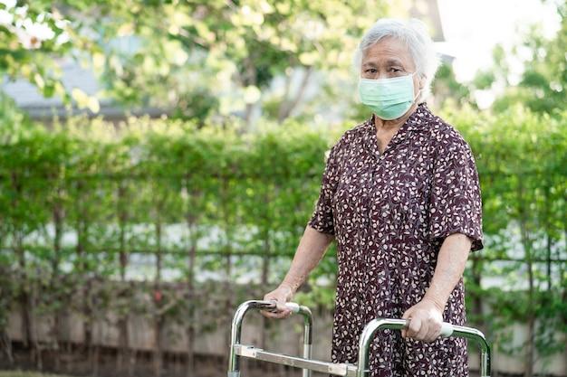 アジアの高齢者または高齢者の老婦人女性患者は、コピースペースの健康的な強力な医療コンセプトを持つ公園で歩行者と一緒に歩く