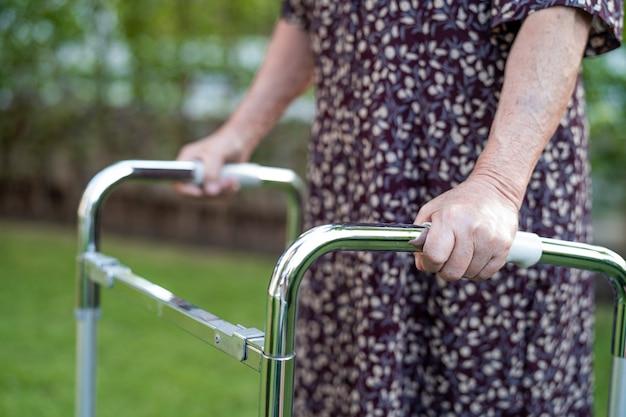 アジアの高齢者または高齢者の老婦人女性患者が公園で歩行者と一緒に歩く