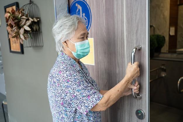 안면 마스크를 쓰고 아시아 노인 또는 노인 노부인 여성 환자가 안전 감염 코로나 바이러스를 보호하기 위해 장애인을 위해 화장실 문을 엽니 다.