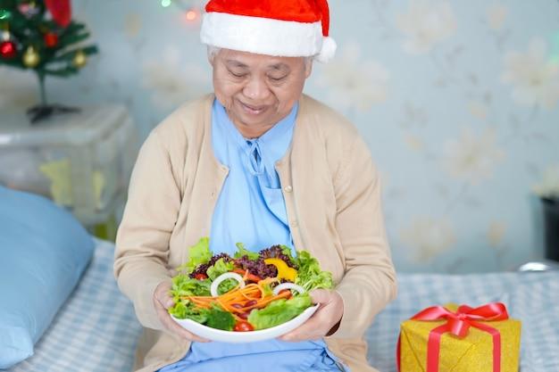 サンタクロースのヘルパー帽子と病院でのクリスマスと新年のお祝い祭の休日のパーティーで非常に幸せな野菜料理を持つアジアのシニアまたは高齢の老婦人女性患者。