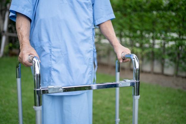 アジアのシニアまたは高齢の老婦人女性は、幸せな新鮮な休日に公園を歩いている間、健康の強い歩行器を使用しています。
