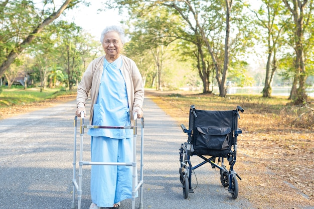 アジアの高齢者や高齢者の老婦人女性が幸せに公園を歩いている間、健康の強い歩行器を使用します