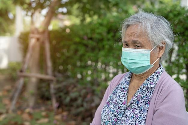 안전 감염 covid-19 코로나 바이러스를 보호하기 위해 집에서 공원에 앉아 얼굴 마스크를 쓰고 아시아 노인 또는 노인 할머니.