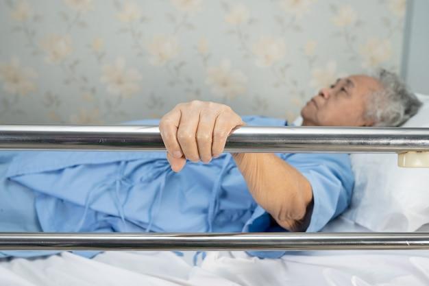 アジアの高齢者または高齢の老婆患者が横になって、病院のベッドに希望を持ってレールベッドを扱います。