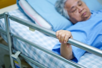 Asian senior or elderly old woman patient lie down handle the rail bed with hope.