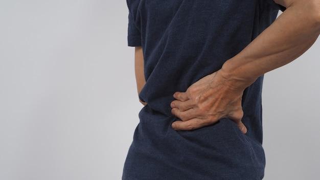 Азиатские старшие или пожилые женщины страдали от боли в спине на белом фоне.