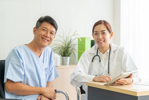 Азиатский старший пациент имея консультацию с доктором